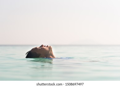 young asian boy floating on a water relaxing in swimming pool.