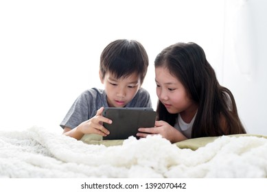 Young Asian boy and girl play a tablet phone on a bed.