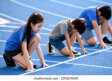 Young Asian boy and girl prepare to start to running on blue track in summer.