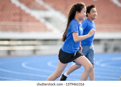 Young Asian boy and girl running on blue track in summer.