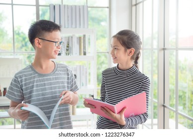Young asian boy and girl talking and smiling in classroom