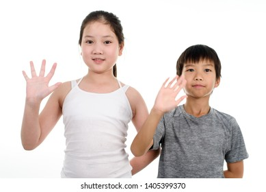 Young Asian boy and girl wave their hand