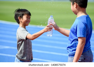 Young Asian boy give a bottle of water to another boy and get a splash water drop with funny moment under the sunlight next to a running track.