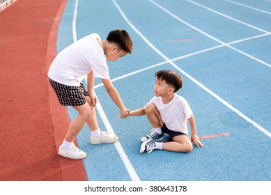 Young asian boy give hand to help accident boy during running on the blue track.