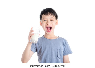 Young asian boy holding a glass of milk over white background
