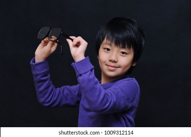 Young Asian boy holding his glasses