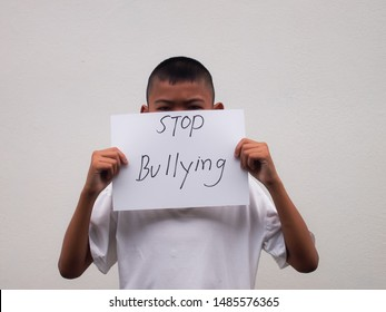 Young Asian boy holding sheet of paper written Stop Bullying standing in front of the white wall background at school .