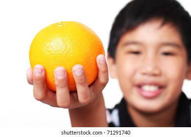 Young asian boy holding/showing a piece of orange fruit. White background.