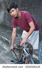 Young asian boy inspecting an old bicycle.