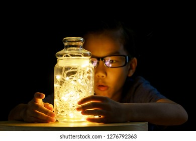 Young Asian boy look at a light bulb in glass container in a darkroom
