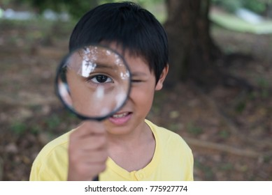 young asian boy looking through magnifying glass. education concept