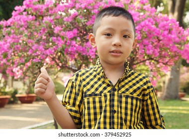Young asian boy on blooming garden background with room for text