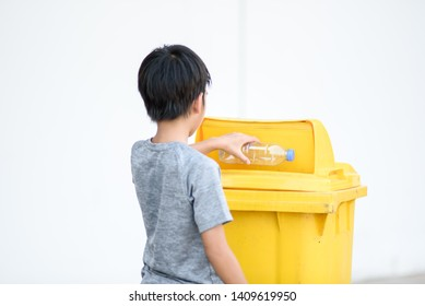 Young Asian boy pick an empty plastic bottle and put in a trash.