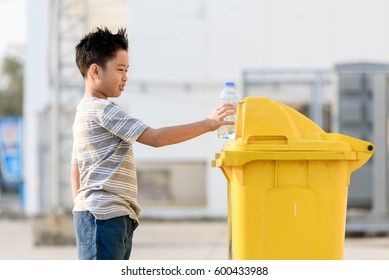 Young Asian boy plastic bottle for eliminate in the yellow bin under the sunlight