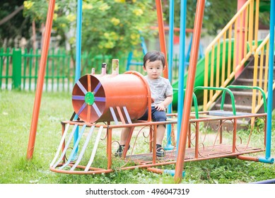 Young Asian boy play a iron train swinging at the playground under the sunlight in summer, Kids play on school yard. Happy kid in kindergarten or preschool. Children having fun at daycare play ground.
