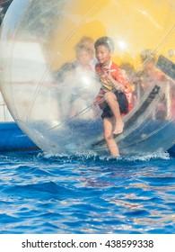 Young Asian boy playing inside a floating water walking ball
