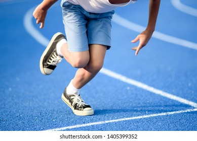 Young Asian boy prepare to start run on a blue track in summer day