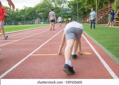 Young Asian boy prepare to start running on red track in the stadium during day time to practice himself.