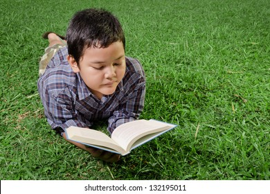 young asian boy reading a book in the park