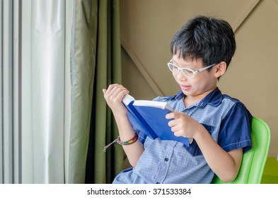 Young Asian boy reading book in room