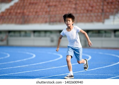 Young Asian boy run on a blue track in summer day