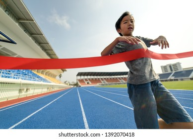 Young Asian boy running on blue track to finished line in summer.