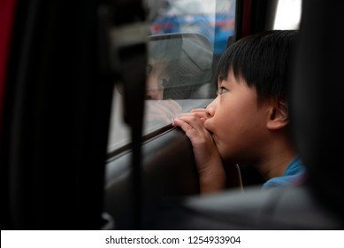 A young asian boy sitting alone looking outside through the car window