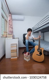 Young Asian boy sitting in his room