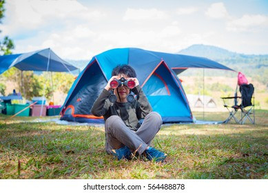 Young asian boy sitting on the ground and looking through binocular searching for birds in camping site