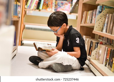 The young Asian boy is sitting on the floor and reading his favorite book in the book store in October, 2017, Thailand.