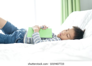 Young asian boy sleeping with his homeworks on a bed during weekend.