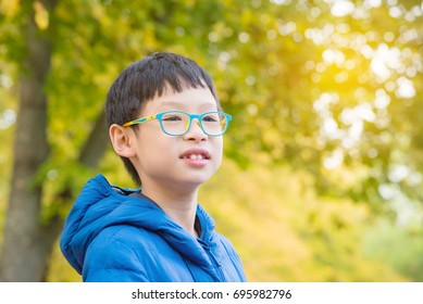 Young asian boy smiling while watching beautiful yellow leaves in autumn park