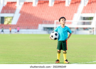 Young Asian boy stand in the grass football field in the stadium during summer.
