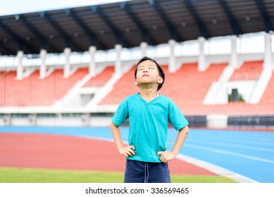 Young Asian boy standing on green football field in stadium during day time and feel relax.