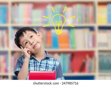 Young Asian boy thinking with bulb in library