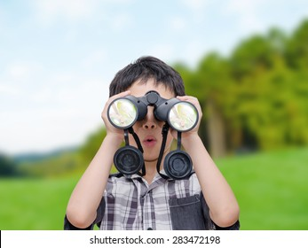 Young Asian boy using binoculars in forest