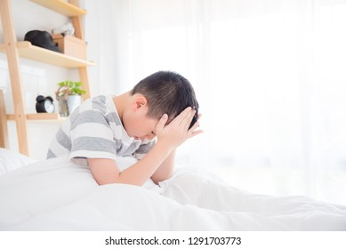 Young asian boy wake up with headache in the morning
