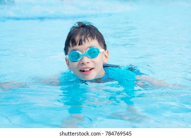Young asian boy wearing goggles swimming in outdoor swimming pool