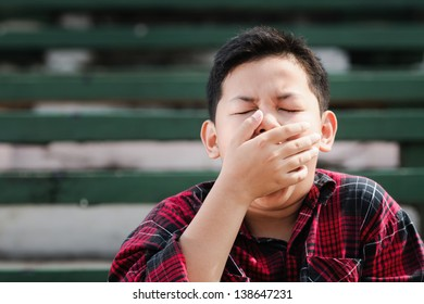 young asian boy yawning with hand covering his mouth