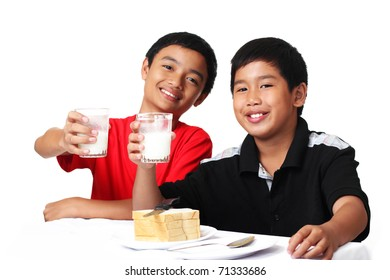 young asian boys holding glasses of milk