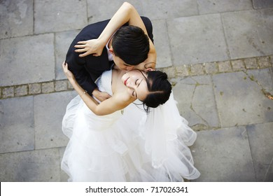 young asian bride and groom embracing kissing dancing, high angle view.