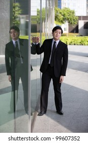 A young Asian business executive leaning on office window.
