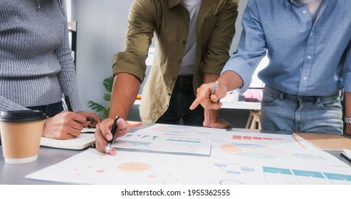 Young Asian business financial team work together in project brainstorm meeting. Cooperate teamwork, strategy planning, small business startup company, or office coworker collaborate concept