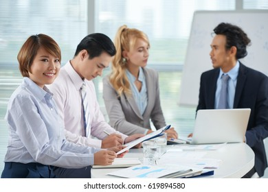 Young Asian business lady at meeting with her colleague