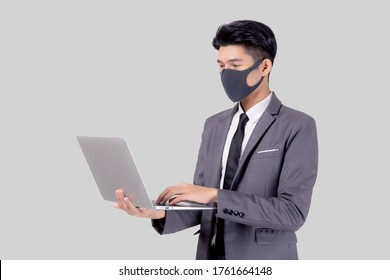 Young asian business man in face mask using laptop computer isolated on white background, quarantine and epidemic covid-19, businessman work from home for health, social distancing, new normal.