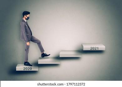 Junge asiatische Geschäftsleute in Gesichtsmaske gehen auf Treppe zum neuen Jahr 2021, während die Krise der pandemischen Covid-19, männlich haben Herausforderung beim wirtschaftlichen Klettern bis zum zukünftigen Jahr 2021 für Erfolg und Erfolg.