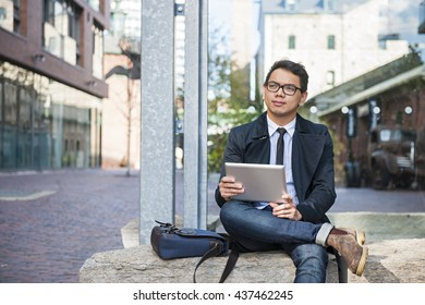 Young  asian business man holding a digital tablet sitting outside on city street looking thoughtful and concerned