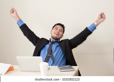 Young Asian business man is raising the hands and smiling after finish his job. Concept of Job Done.