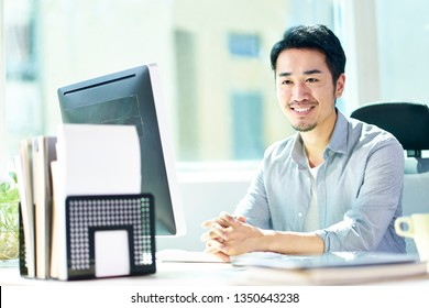 young asian business man sitting by desk in front of desktop computer looking at camera smiling.