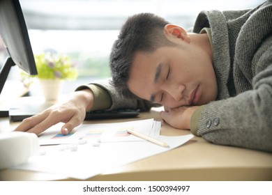 Young asian business man sleeping in office with lot of medicines on his work desk. Health problem worker.